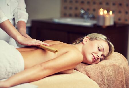 spa beauty: people, beauty, spa, healthy lifestyle and relaxation concept - close up of beautiful young woman lying with closed eyes and having bamboo massage in spa
