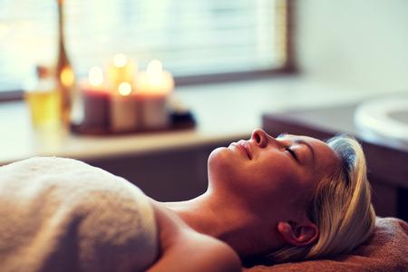 relajado: personas, belleza, spa, estilo de vida saludable y el concepto de relajación - hermosa mujer joven tendido con los ojos cerrados en el spa