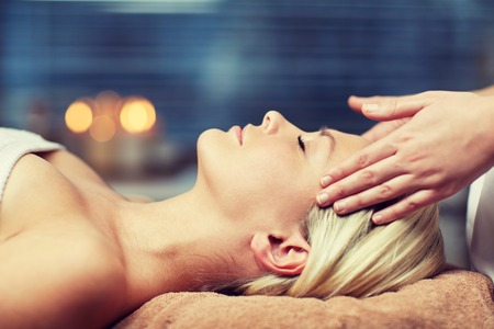 healthcare and beauty: people, beauty, spa, healthy lifestyle and relaxation concept - close up of beautiful young woman lying with closed eyes and having face or head massage in spa Stock Photo