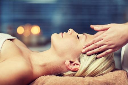 salon de belleza: personas, belleza, spa, estilo de vida saludable y la relajación concepto - cerca de la hermosa mujer joven tendido con los ojos cerrados y tener cara o la cabeza de masaje en el spa