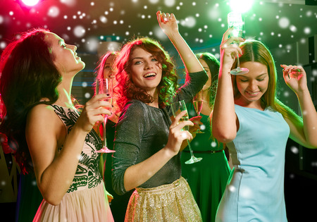 dancing club: new year party, holidays, celebration, nightlife and people concept - smiling friends with glasses of non-alcoholic champagne dancing in club and snow effect