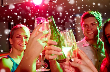 nonalcoholic beer: new year party, holidays, celebration, nightlife and people concept - smiling friends clinking glasses of non-alcoholic champagne in club and snow effect