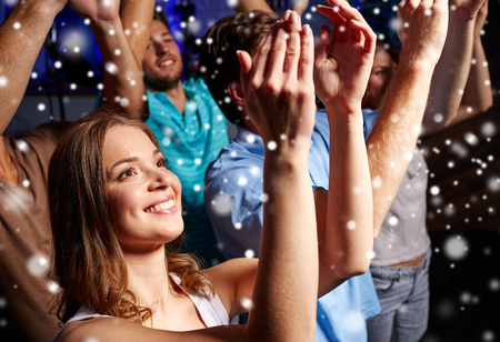 happy crowd: party, holidays, celebration, nightlife and people concept - smiling friends applauding at concert in club and snow effect