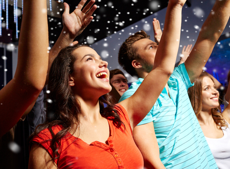 riendo: fiesta, días de fiesta, celebración, vida nocturna y la gente concepto - amigos sonrientes que agitan las manos en el concierto en el club y la nieve efecto