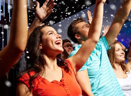 party, feiertage, feier, Nachtleben und Personen-Konzept - l�chelnde Freunde winkenden H�nde bei Konzert in Club und Schnee-Effekt