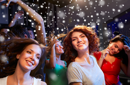 clubbers: party, holidays, celebration, nightlife and people concept - smiling friends dancing at concert in club and snow effect