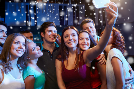 party, technology, nightlife and people concept - smiling friends with smartphone taking selfie in club and snow effect Stock Photo