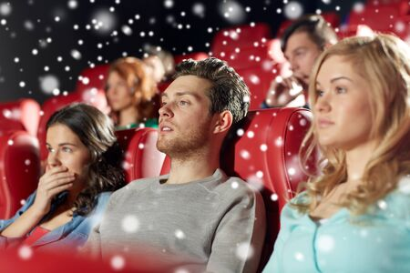 christmas movies: cinema, entertainment and people concept - friends watching horror, drama or thriller movie in theater over snowflakes Stock Photo