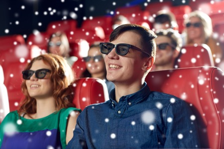 christmas movies: cinema, entertainment and people concept - happy friends or couple with 3d glasses watching movie in theater over snowflakes Stock Photo