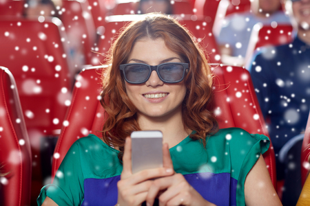 winter theater: cinema, technology, entertainment and people concept - happy woman in 3d glasses reading message on smartphone in movie theater with friends over snowflakes