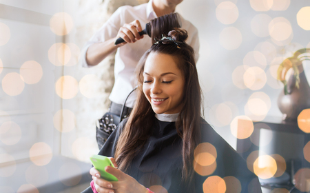 salon: beauty, hairstyle and people concept - happy young woman with smartphone and hairdresser making hair styling at salon over holidays lights