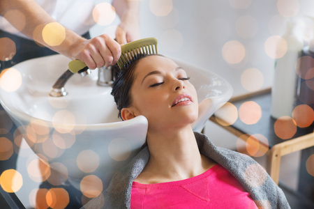 wet: beauty, hair care and people concept - happy young woman with hairdresser combing wet hair after washing at salon over holidays lights Stock Photo