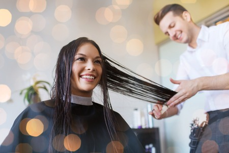 beauty, hairstyle and people concept - happy young woman and hairdresser cutting hair tips at salon over holidays lights