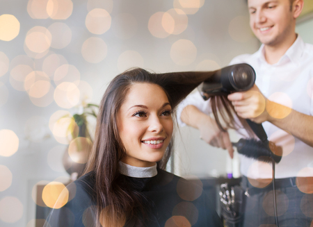 woman hairstyle: beauty, hairstyle and people concept - happy young woman and hairdresser with fan making hot styling at hair salon over holidays lights Stock Photo