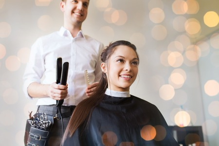beauty shop: beauty, hairstyle and people concept - happy young woman with hairdresser curling hair and making hairdo at salon over holidays lights Stock Photo