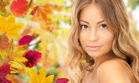 la beauté, les gens, la saison et le concept de santé - beau visage jeune femme aux longs cheveux bouclés sur les feuilles d'automne fond Banque d'images