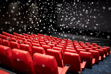 hollywood christmas: entertainment and leisure concept - movie theater or cinema empty auditorium with red seats over snowflakes