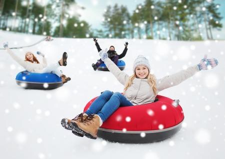 happy young: invierno, el ocio, el deporte, la amistad y el concepto de la gente - grupo de amigos felices deslizarse sobre los tubos de nieve