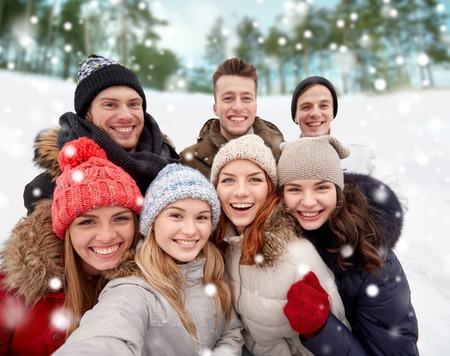 family and friends: winter, technology, friendship and people concept - group of smiling men and women taking selfie outdoors
