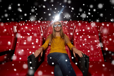 empty of people: cinema, technology, entertainment and people concept - young woman with 3d glasses watching movie alone in empty theater auditorium over snowflakes