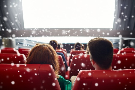 back screen: cinema, entertainment, leisure and people concept - couple watching movie in theater from back over snowflakes Stock Photo