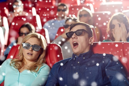 christmas movies: cinema, technology, entertainment and people concept - scared friends or couple with 3d glasses watching horror or thriller movie in theater with snowflakes