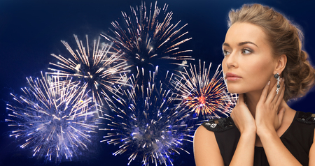 woman night: people, holidays and glamour concept - beautiful woman wearing earrings over firework on dark blue background