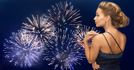 hollywood christmas: people, holidays, party, jewelry and glamour concept - beautiful woman with diamond earring over firework lights on dark blue sky  background