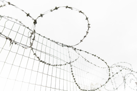 martial law: imprisonment, restriction concept - barb wire fence over gray sky