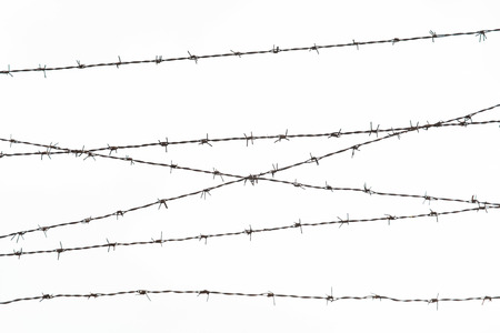 concentration camp: imprisonment, restriction concept - barb wire fence over gray sky