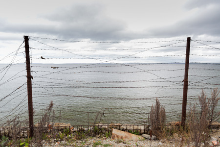 imprisonment: imprisonment, restriction concept - barb wire fence over gray sky and sea