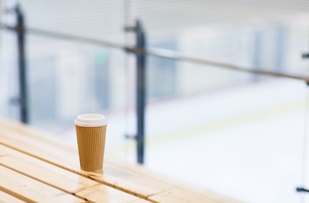 skating rink: hot drink, winter and leisure concept - close up of coffee cup on wooden bench at skating rink Stock Photo