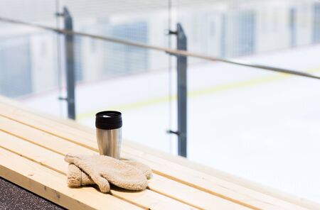 thermos: hot drink, winter and leisure concept - close up of thermos cup and sheepskin mittens on bench at ice rink arena
