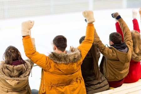teenage guy: people, friendship, sport and leisure concept - happy friends watching hockey game or figure skating performance on ice rink arena Stock Photo