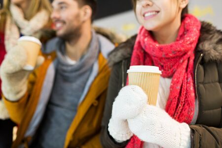 cups of coffee: people, friendship, hot drinks and leisure concept - close up of happy friends drinking from paper coffee cups on skating rink