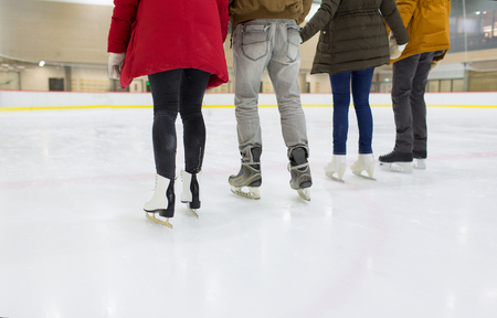 ice arena: people, friendship, sport and leisure concept - close up of happy friends skating on ice rink