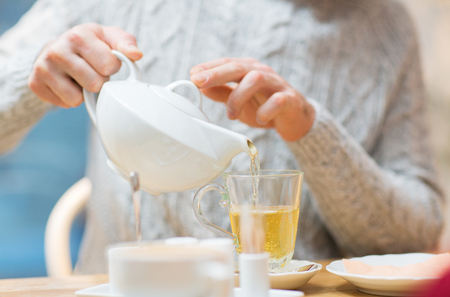 people, leisure and drinks concept - close up of man pouring tea from pot to cup at cafe
