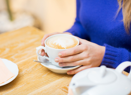 girl sitting: people, leisure and drink concept - close up of woman with coffee cup at cafe