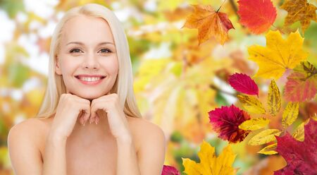health beauty: beauty, people, season and health concept - beautiful young woman touching her face over autumn leaves background