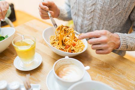 pasta: gente, el ocio y el concepto de comida - close up hombre de pasta de comer para la cena en el restaurante o en el hogar