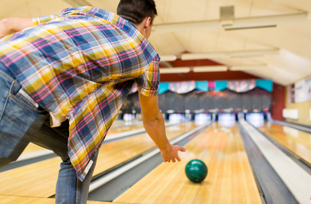 leisure game: people, leisure, sport and entertainment concept - close up of young man throwing ball to alley in bowling club