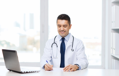 working desk: medicine, profession, technology and people concept - smiling male doctor with laptop in medical office Stock Photo