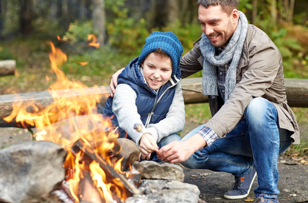in the woods: camping, tourism, hike, family and people concept - happy father and son roasting marshmallow over campfire
