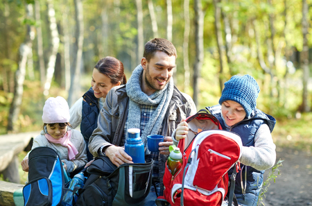 thermos: camping, travel, tourism, hike and people concept - happy family with backpacks and thermos at camp