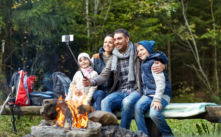 woods: camping, travel, tourism, hike and people concept - happy family sitting on bench and taking picture with smartphone on selfie stick at campfire in woods