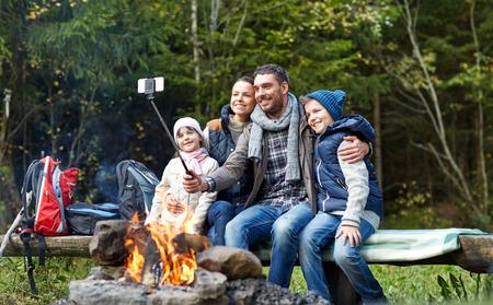 fogatas: camping, viajes, turismo, ir de excursión y el concepto de la gente - familia feliz sentado en el banco y la toma de fotografías con el teléfono inteligente en el palillo autofoto en la hoguera en el bosque Foto de archivo