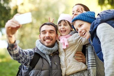 persona viajando: viajes, turismo, ir de excursión, la tecnología y el concepto de la gente - la familia feliz con mochilas que toman selfie por teléfono inteligente al aire libre