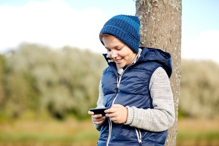 people, children and technology concept - happy teenage boy playing game or texting message on smartphone outdoors Stock Photo