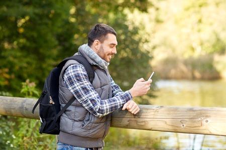 uomo felice: viaggi, turismo, escursioni, la tecnologia e le persone concetto - l'uomo felice con zaino e smartphone all'aperto Archivio Fotografico