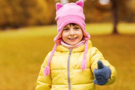 beautiful preteen girl: autumn, childhood, happiness, gesture and people concept - happy beautiful little girl showing thumbs up outdoors Stock Photo